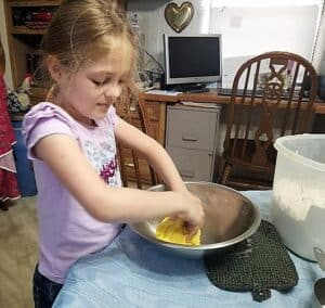 Our granddaughter helping me color the dough